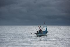 Lonely Fisherman. Fisherman with his small boat on a cloudy morning Stock Photography