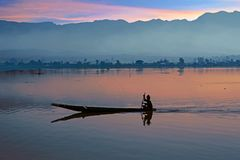 Lonely fisherman fishing at sunrise on a lake in Myanmar. Asia at sunset Stock Images