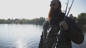 Bearded fisherman with long beard walks on the river bank with fishing rods. Slow motion. Lonely fisherman with long beard walks on the river bank with fishing stock video footage