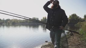 Lonely fisherman with long beard walks on the river bank with fishing rods. Slow motion. Lonely fisherman with long beard walks on the river bank with fishing stock video footage