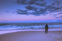 Lonely fisherman on shore of ocean royalty free stock image