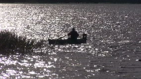 Lonely fisherman silhouette in boat and  light stock video footage