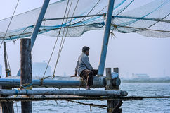 Lonely fisherman sitting on a wooden fishing platform stock photos