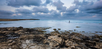 Lonely fisherman standing in the water at Dor Beach, Israel. Lonely fisherman standing in the water at sunrise, at Dor Beach, Israel royalty free stock photos