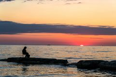 Lonely fisherman on a stone beach on a sunset background royalty free stock photography