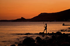 Lonely Fisherman At Sunset Royalty Free Stock Photos