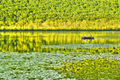 Lonely fishing boat in a beautiful lake. With father and sons fishing and talking royalty free stock images