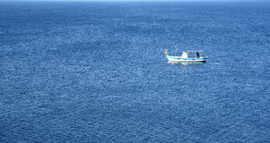 Lonely fishing Boat on a calm blue sea Stock Photos