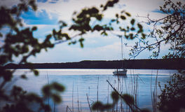 Lonely fishing boat on Calm lake Stock Images