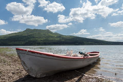 Lonely fishing boat on lake with cloudy sky Stock Image