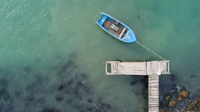 Lonely fishing boat and wooden pier in turquoise ocean, sea. Aerial photo, top view. Lonely fishing boat and wooden pier in turquoise ocean. Aerial photo, top Stock Photo