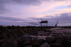 Lonely fishing house. Under purple cloudy sunset, a lonely fishing house surround by grey rocks Royalty Free Stock Images