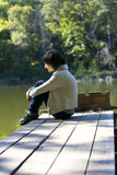 Lonely Girl. Siiting at the river at daylight stock photo