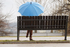 Lonely girl with blue umbrella siting on bench Stock Photography