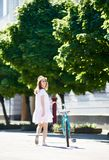 Lonely girl comes with retro bicycle on sunny city street. Lonely girl comes with a retro bicycle on the sunny city street with green spaces. The girl turned to Stock Photography