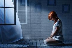 Lonely girl in a dark room royalty free stock photo