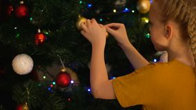 Lonely girl hanging ball on Christmas tree in orphanage, thinking about family stock footage