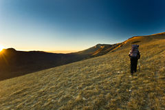 Lonely girl hiking in the mountains at sunrise Royalty Free Stock Images
