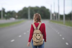 Lonely girl hitchhiking on the road with a backpack. stock images