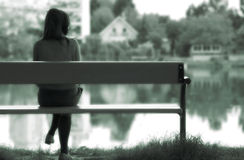 Lonely girl by the lake. Young lonely girl, lost in memories, is sitting on a bench next to a calm lake Stock Images