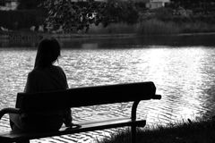Lonely girl by the lake. Young lonely girl, lost in memories, is sitting on a bench next to a calm lake Stock Photo