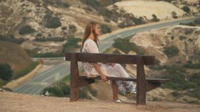 Lonely girl in long white dress sitting at the bench. Beautiful rocky hills and road are in the background. Laisure of. Lonely girl in long white dress sitting stock video footage
