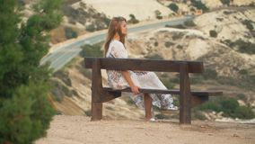 Lonely girl in long white dress sitting at the bench. Beautiful rocky hills and road are in the background. Laisure of. Lonely girl in long white dress sitting stock video