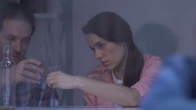Lonely girl looking in window, parents drinking alcohol on background, addiction. Stock footage stock video