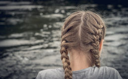Lonely girl with pigtails. Little girl  resting on the river Bank. Loneliness and sadness Stock Photography