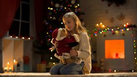 Lonely girl playing with teddy bear, abandoned by parents working at Christmas. Stock photo stock images