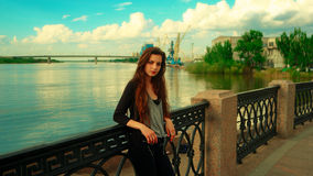 LOnely girl posing leaning back against embankment fence and background with river and wharf cranes Stock Photography