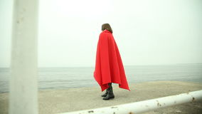 Lonely girl in red blanket looking at the sea Stock Images