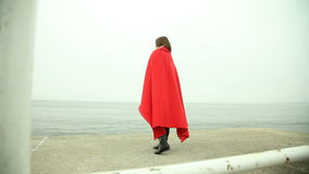 Lonely girl in red blanket looking at the sea Stock Photos