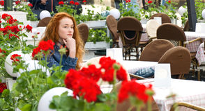 Lonely girl with red hair sitting in a cafe Stock Photography