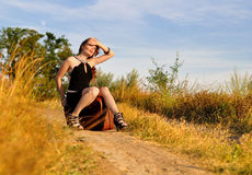 Lonely girl sit on suitcase at country road Royalty Free Stock Photos