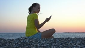 The girl on the beach with the phone. A lonely girl sits by the sea on a pebbly beach at sunset and works with a phone stock footage