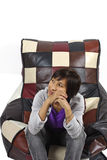 Lonely girl sits on the sofa at studio Stock Photos