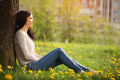 The lonely girl sits at a tree looks in a distance Royalty Free Stock Image