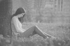 The lonely girl sits at a tree. The photo in old black-and-white Royalty Free Stock Photography