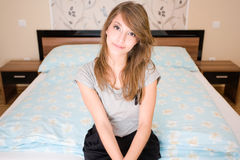 Lonely girl sitting on the bed. Royalty Free Stock Photo