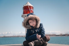 Lonely girl sitting near the harbor beacon light. A sad lonely little girl sitting near the harbor beacon light on sunny fresh, cold day Stock Photos