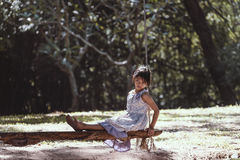 The lonely girl. Sitting on a swing at The park Royalty Free Stock Photos
