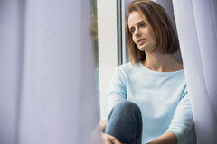 Lonely girl sitting at the window Royalty Free Stock Images