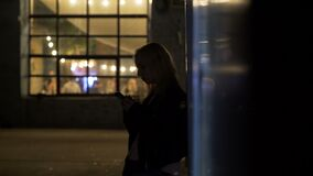Lonely girl standing on alley near nightclub and calling taxi, night life. Stock footage stock footage