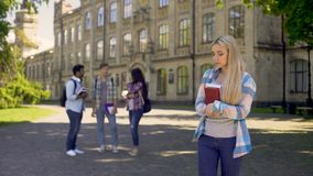 Lonely girl standing away from friends, upset about gossips at university. Stock footage stock video footage
