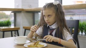 Student elementary school in a school uniform sitting at a table in the school cafeteria and eat. stock footage