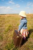 Lonely girl with suitcase. Back view Stock Photo