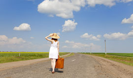 Lonely girl with suitcase at country road. Royalty Free Stock Image