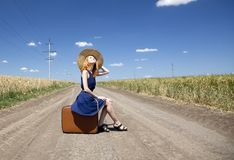 Lonely girl with suitcase at country road. Royalty Free Stock Photos