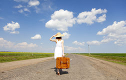 Lonely girl with suitcase at country road. Stock Photos